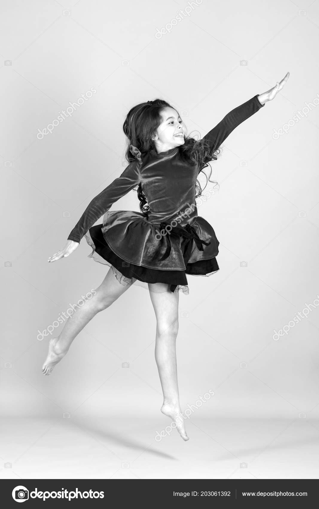 b7ae9909650 Sólo la danza. belleza y moda. bailarina de niña de poco salto sobre fondo  azul. Danza infantil en vestido rojo descalzo. Concepto de infancia feliz.