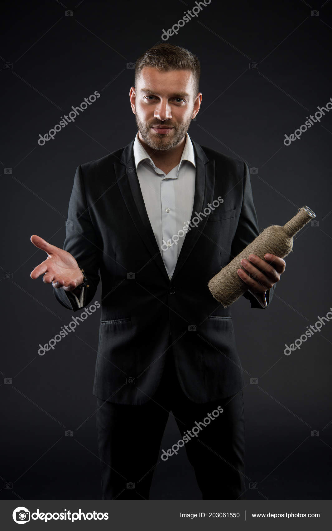 Gran inauguración del restaurante. Hombre de traje oscuro con vintage  botella en las manos. Macho con confianza mira aislado sobre fondo negro. be34f595b4e