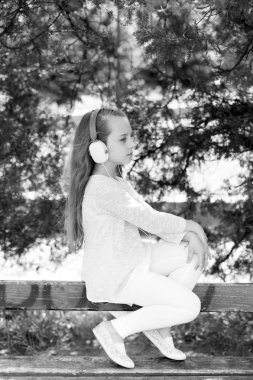 Fashion kid and modern technology. Little girl listen music in summer park. Child enjoy music in headphones outdoor. Melody sound and mp3. Summer vacation and fun
