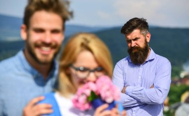 Lovers hugs outdoor flirt romance relations. Couple in love dating while jealous bearded man watching wife cheating him with lover. Couple romantic date lovers bouquet flowers. Infidelity concept