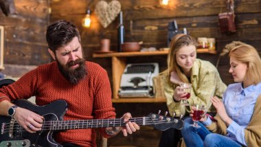 Man with long bushy beard singing passionately, music concept. Girls drinking tea or wine and enjoying lovely tunes. Bearded man playing guitar. Guitarist with hipster beard performing new song