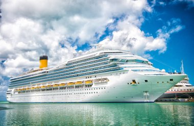 cruise ship at sea dock in turquoise sea on cloudy blue sky. Travelling by sea. Water transport and transportation. Wanderlust and summer vacation