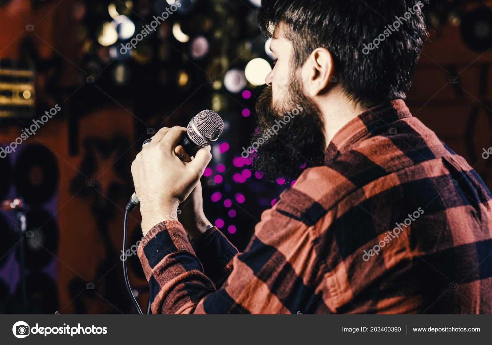 Musician with beard singing song in karaoke, rear view  Man in