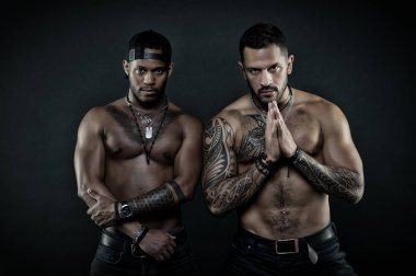 Sportsmen with sexy fit torsos. Martial arts contestants calming down before fight. Bodybuilders isolated on black background. Hispanic man with geometrical tattoos holding hands in prayer gesture