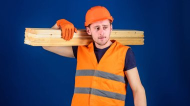 Man in helmet, hard hat and protective gloves holds wooden beam, blue background. Carpenter, woodworker, strong builder on thoughtful face carries wooden beam on shoulder. Wooden materials concept