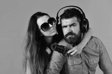 Man with beard and girl hug on grey background.