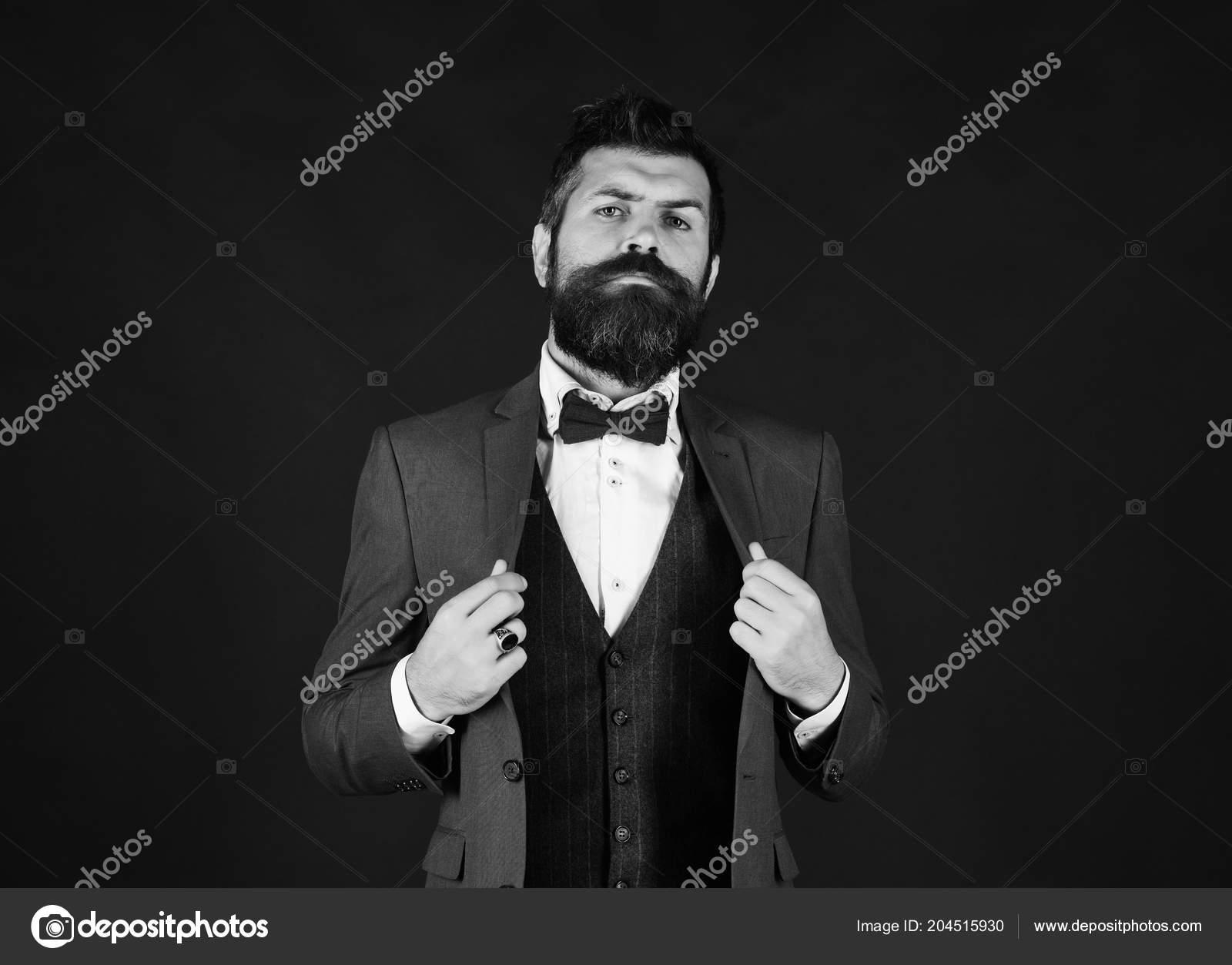 9ced78391099 Uomo d'affari con lieto viso regola giacca. Uomo in vestito elegante retrò  e gilet su fondo marrone. Direttore o imprenditore con elegante barba e  baffi ...