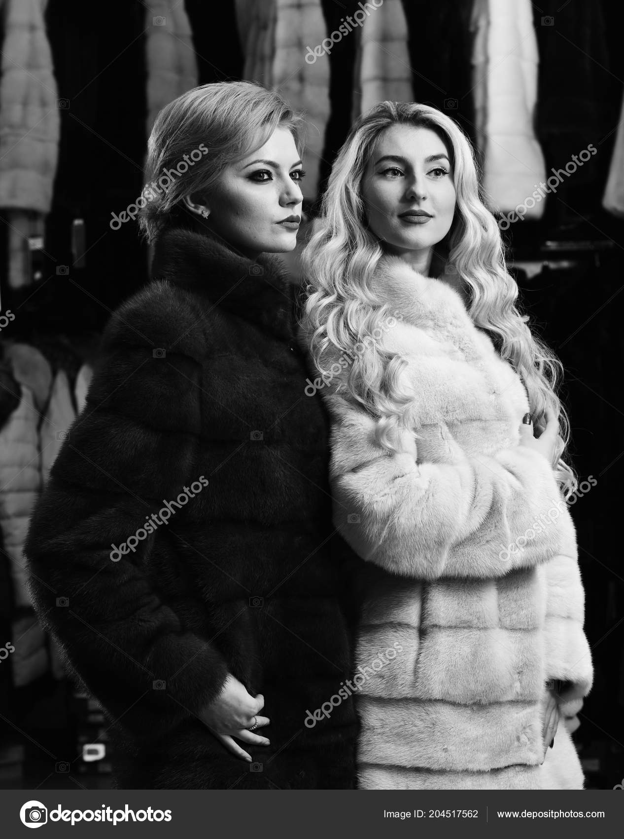Girls With Strict Faces In Black And White Fur Coats Stock Photo