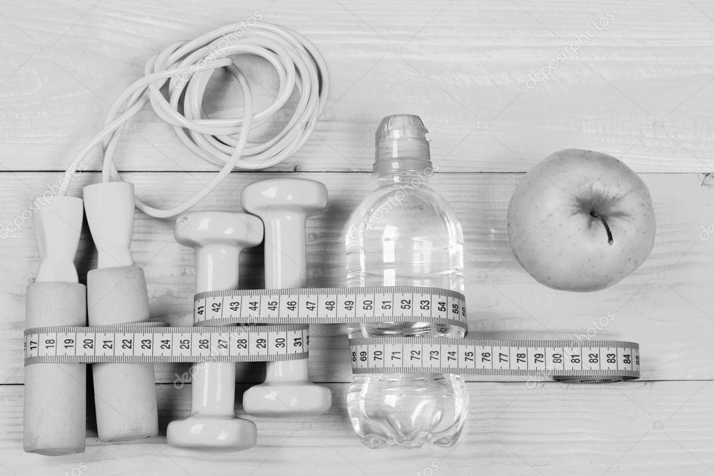Measuring tape, jump rope and dumbbells, top view
