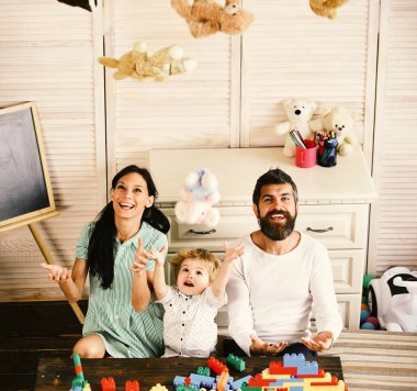 Parents and son with happy faces play with soft toys