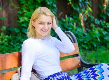 Peace and tranquility. Why you deserve break. Woman blonde take break relaxing in park. Girl sit bench relaxing in shadow, green nature background. Ways to give yourself break and enjoy leisure