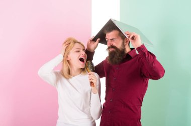 Better sing at talent show than at work. Lady imagine she is superstar talented singer. Singing is her passion. Lady sing using hair brush as microphone while man annoyed hiding under laptop