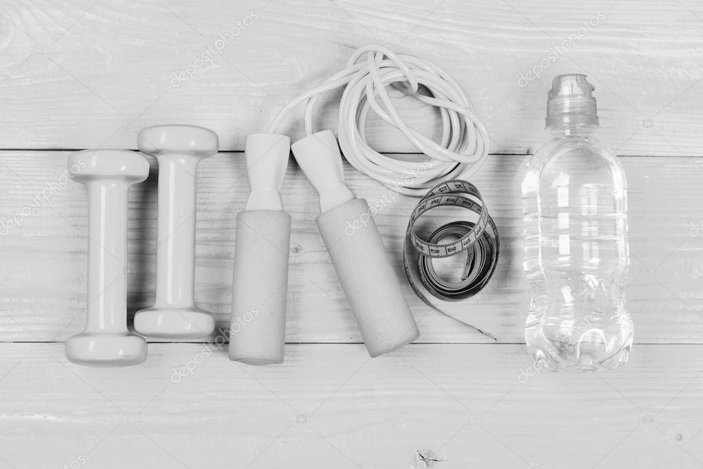 Dumbbells, measuring tape, jump rope and water bottle, top view