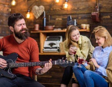 Musician putting all heart into his art. Bearded man singing passionately love song. Girls enjoying touching performance of bearded guitarist. Hipster with bushy beard playing electronic guitar