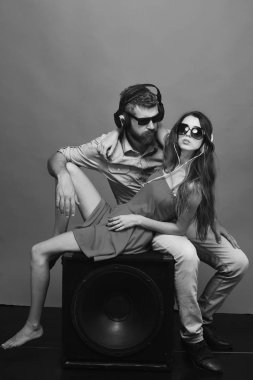 Man with beard wears headphones and sunglasses. Technologies and music concept. Couple in love lies on loudspeaker