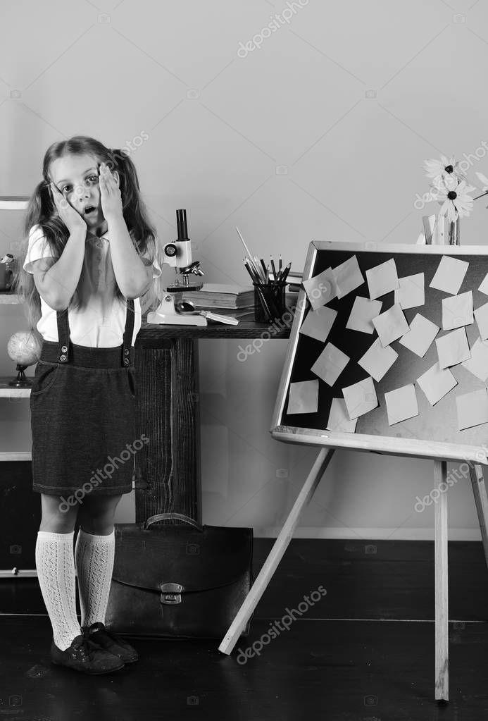 Schoolgirl with worried face in her classroom