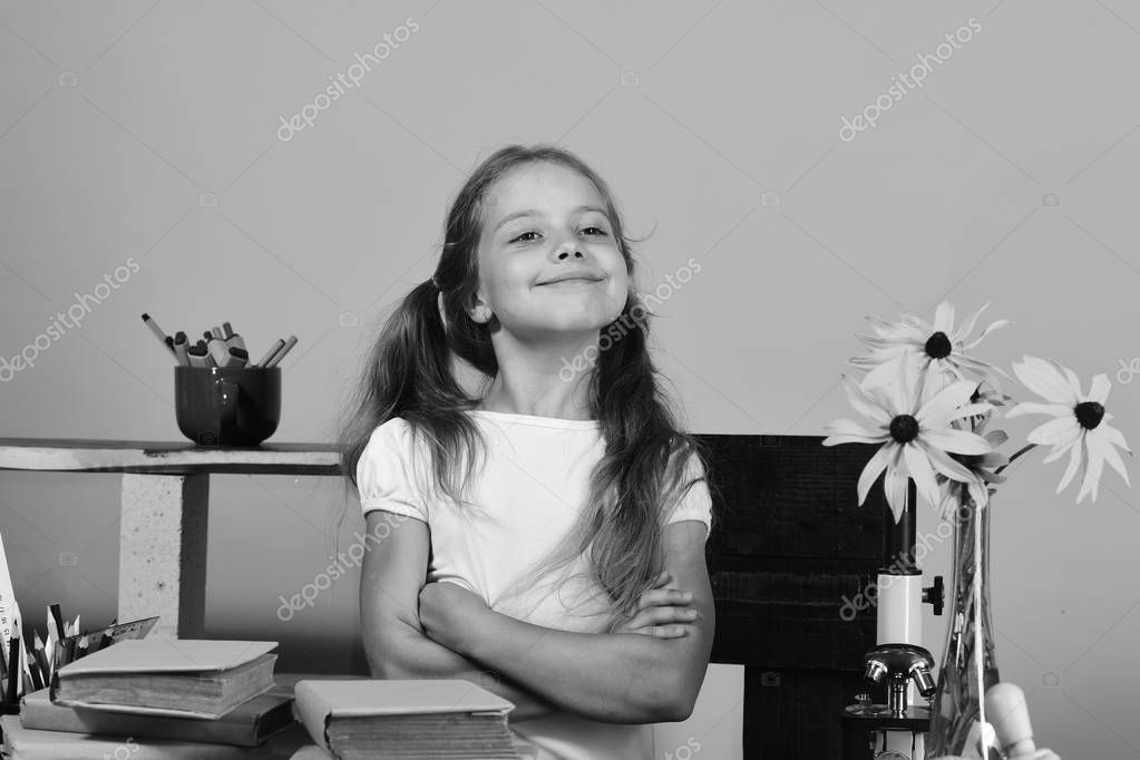 Girl stands at her desk with colorful stationery, books and flowers. Kid and school supplies on pink wall background