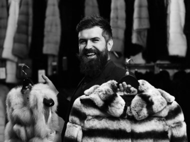 Man with happy face holds furry coats with clothes rack on background. Fashion and shopping concept. Businessman with expensive overcoats.