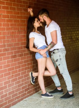 Desire and temptation. Girl and hipster strong desire feeling. Couple find place to be alone. Couple enjoy intimacy moment without witnesses. Couple in love full of desire brick wall background