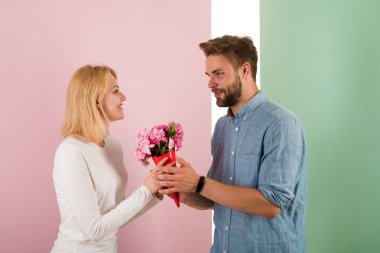 Man congratulates woman birthday anniversary holiday, pastel background. Gift concept. Man gives bouquet flowers to girlfriend. Couple date bouquet flowers gift. Couple in love celebrating holiday