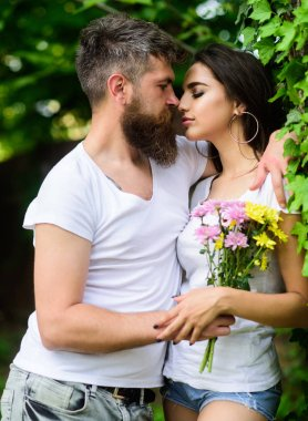 Man bearded hipster hugs gorgeous girlfriend. Couple love romantic date nature park background. Love relations romantic feelings. Gentle kiss. Couple in love going to kiss. Pleasant romantic kiss. stock vector