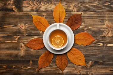Hot beverage on saucer on wooden background