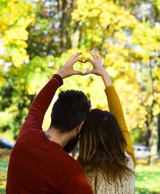 Man and woman turned backwards on autumn trees background.