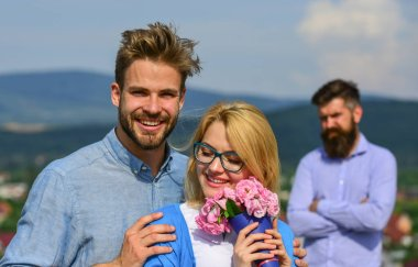 Couple in love dating while jealous bearded man watching wife cheating him with lover. Lovers hugs outdoor flirt romance relations. Couple romantic date lovers bouquet flowers. Infidelity concept