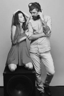 Man with beard wears headphones.Couple in love