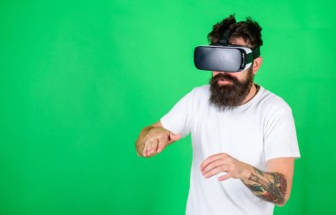 Man with beard in VR glasses, green background. Hipster on busy face use modern technologies for entertainment or education. Guy DJ with VR glasses play music with mixing console. VR musician concept