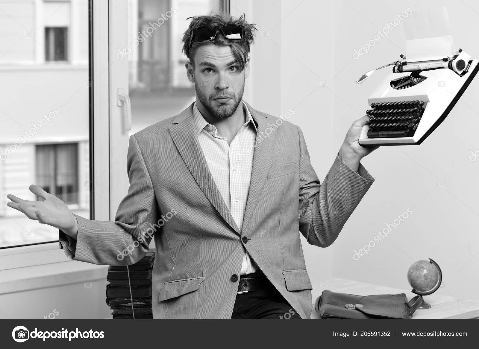 Man with puzzled face types business report  Young author or editor