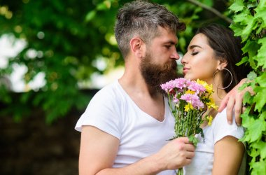Gentle kiss. Man bearded hipster hugs gorgeous girlfriend. Couple love romantic date nature park background. Love relations romantic feelings. Couple in love going to kiss. Pleasant romantic kiss. stock vector