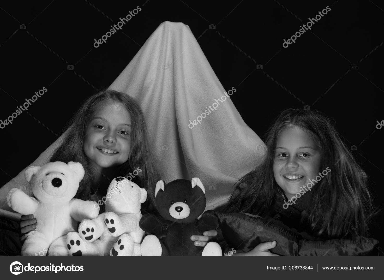 Girls with happy faces playing with teddies. Children and fun time concept. Friends  having fun with toys in blanket tent. Kids wearing red jammies in bed on ... 268aab824