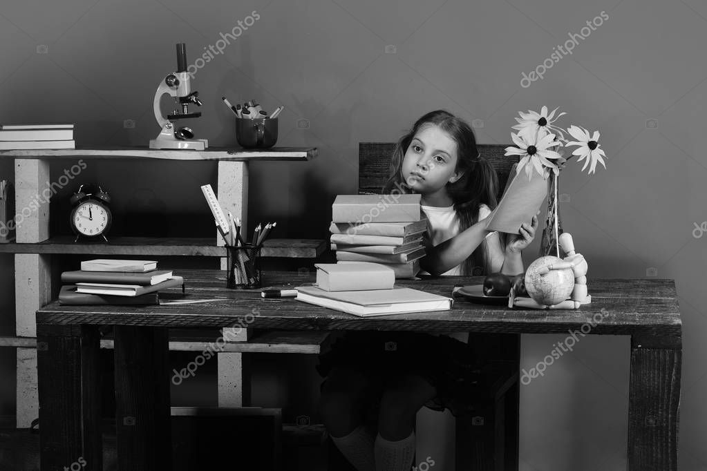 Schoolgirl with tired face holds textbook. Kid and school supplies on green wall background