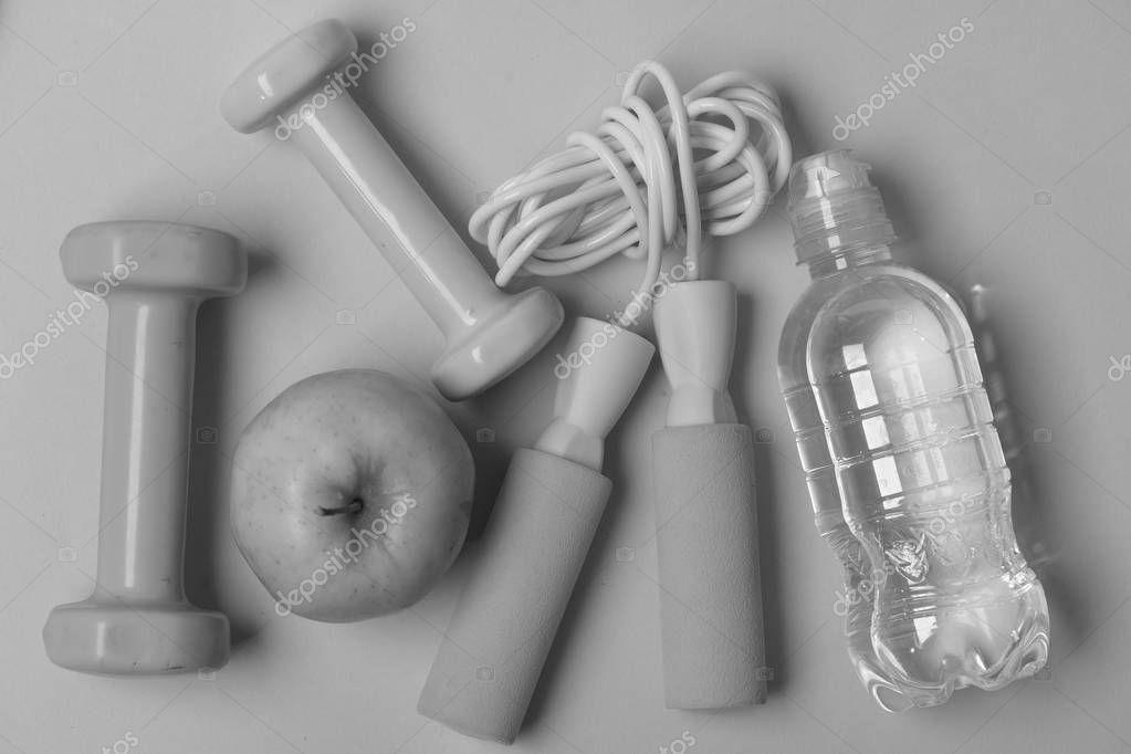 Fit shape and sport concept. Jump rope, apple and barbells next to water bottle