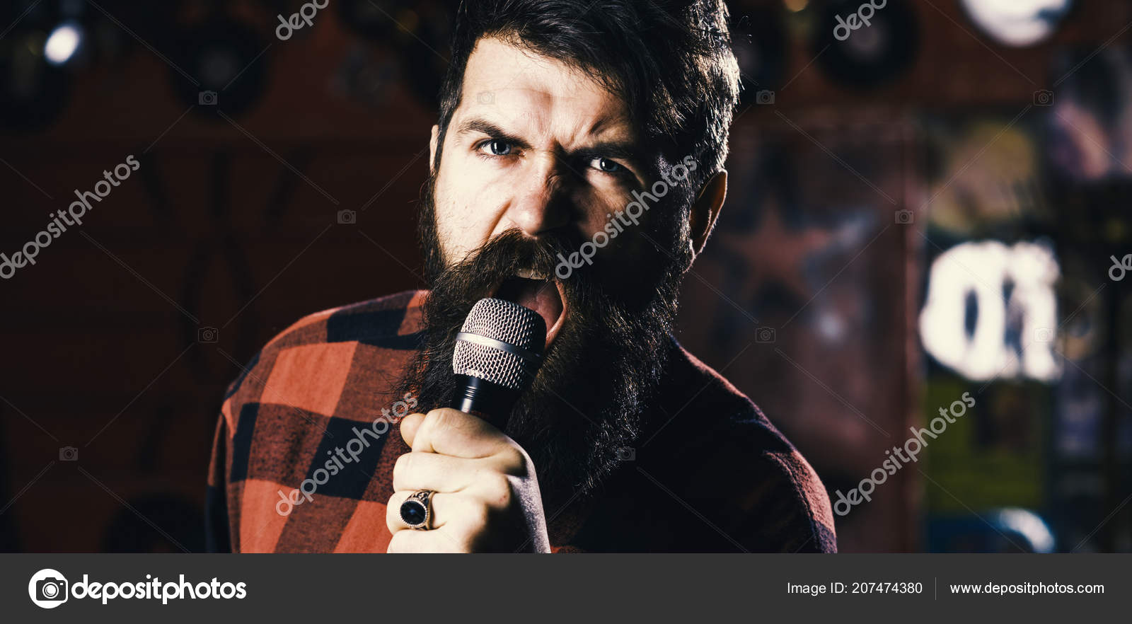 Man with agressive face holds microphone, singing song, karaoke club