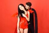 Paar in der Liebe spielen Rollenspiel. Vampire Opfer Konzept. Mann und Frau gekleidet wie Vampir, Dämon, roter Hintergrund. Vampir im Mantel hinter sexy Teufel Mädchen. Vampir beißt weiblichen Hals