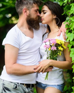 Man bearded hipster hugs gorgeous girlfriend. Couple in love going to kiss. Pleasant romantic kiss. Couple love romantic date nature park background. Love relations romantic feelings. Gentle kiss. stock vector