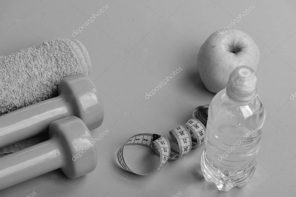 Athletics and weight loss concept. Barbells and towel near apple