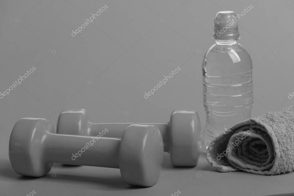 Dumbbells in bright green color, water bottle and cloth