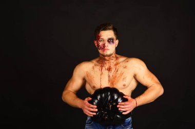Guy with blood on face and chest, copy space. Autumn season and seduction concept. Man with serious face and muscular torso on black background. Macho with torso holds pumpkin in both hands. stock vector
