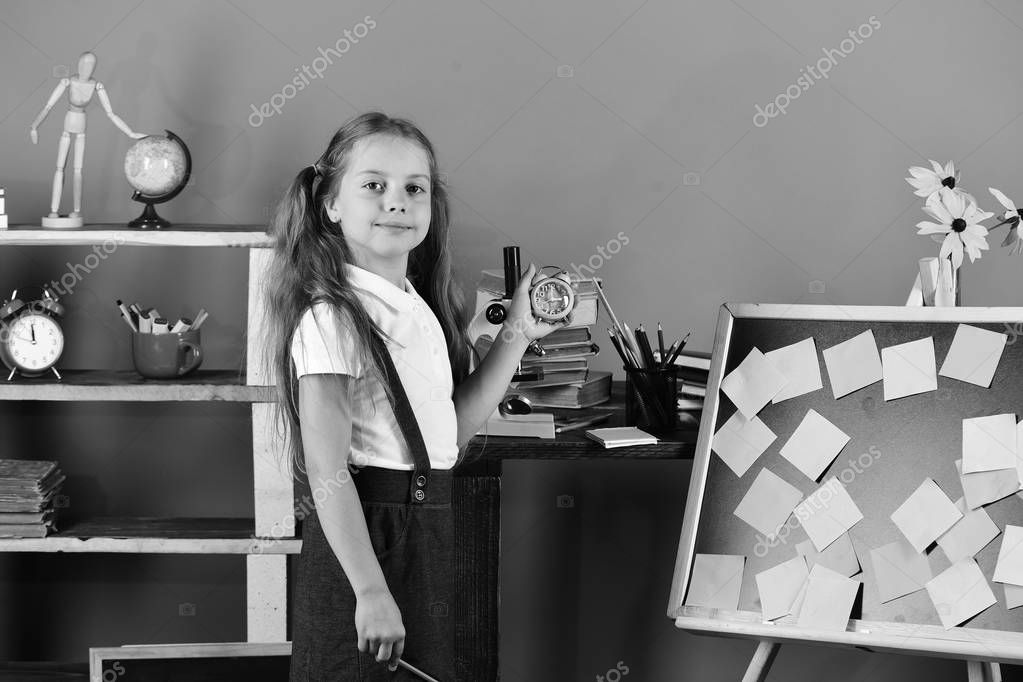 Girl with ponytails stands by blackboard with sticky notes. Kid and school supplies on green wall background