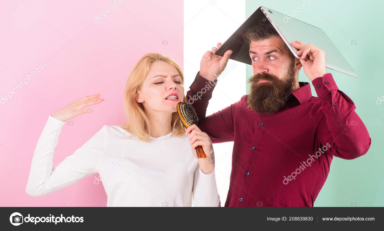 Señora horrible voz cantar utilizando cepillo de pelo como micrófono  mientras que hombre molesto escondido debajo del ordenador portátil. 70d010bbd436