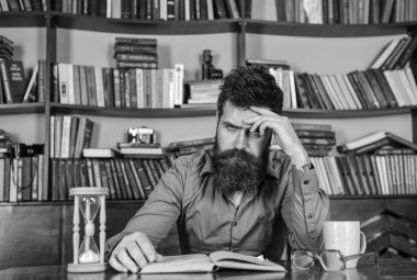 Man on concentrated face reading book, studying, bookshelves on background. Self education concept. Man sits at table with mug and hourglass. Teacher or student with beard studying in library