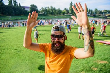 Happy to meet you. Man bearded hipster in front of crowd people waving hand green riverside background. Urban event celebration. Hipster in cap happy to meet friend at event picnic fest or festival