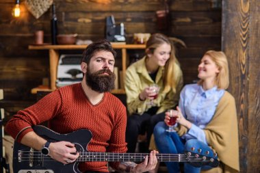 Man with stylish beard enjoying creative process. Musician entertaining his wife and daughter. Girls with smiling face listening to music, happiness concept. Bearded man in red sweater playing guitar