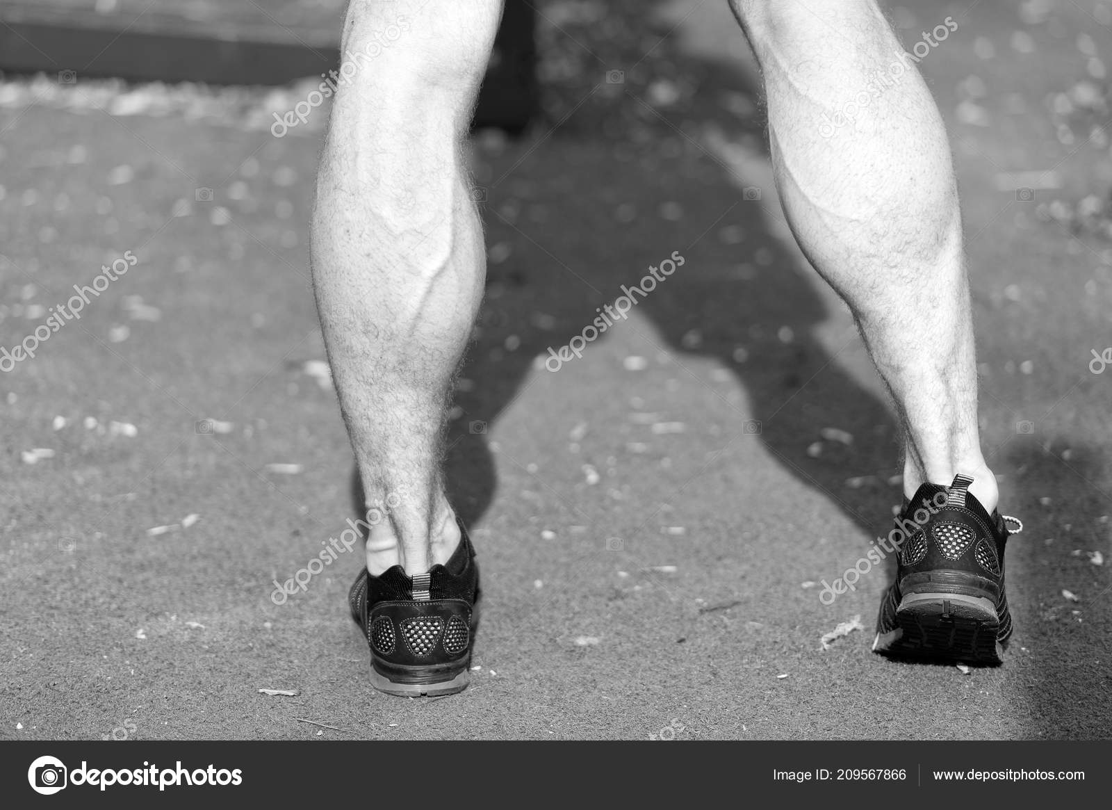 Feet In Black Sport Fashion Shoes On Green Grass Muscular Legs With