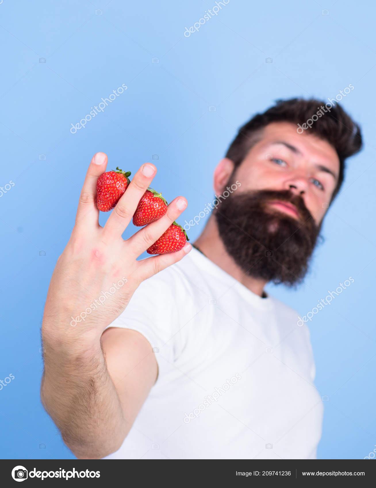 Fresas de hipster de barba de hombre entre los dedos azul de fondo. Fresa  repleto de antioxidantes de la vitamina C fibra. Beneficios nutricionales  de la ... df79a4ebd37