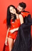 Vampir beißt weiblichen Hals. Vampir im Mantel hinter sexy Teufel Mädchen. Paar in der Liebe spielen Rollenspiel. Vampire Opfer Konzept. Mann und Frau gekleidet wie Vampir, Dämon, roter Hintergrund