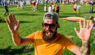 Hipster in cap happy to meet friend at event picnic fest or festival. Man bearded hipster in front of crowd people waving hand green riverside background. Happy to meet you. Urban event celebration